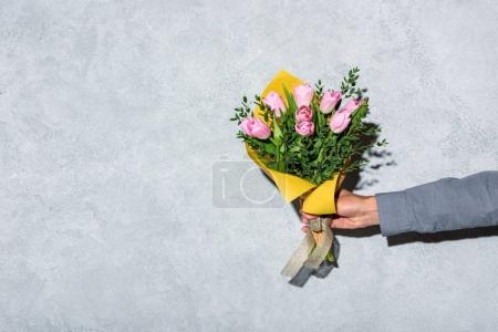 Close-up view of man giving bouquet of flowerson grey background