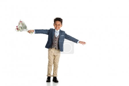 happy african american boy standing with bouquet and open arms on white