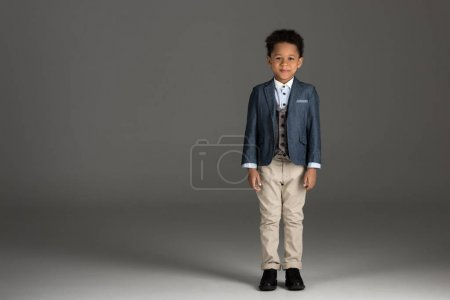 adorable african american boy standing in suit on gray