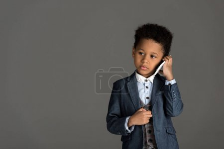 adorable african american kid talking by smartphone isolated on gray