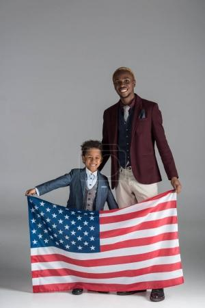 african american family looking at camera while boy holding american flag in hands on grey background