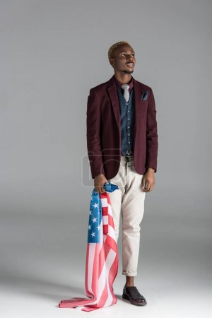 african american with american flag in hand looking upwards on grey background