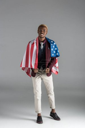 smiling african american man with american flag on shoulders  looking at camera isolated on grey