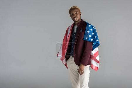 african american man with american flag on shoulders  looking at camera isolated on grey