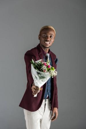 smiling african american man with bouquet in hand isolated on grey
