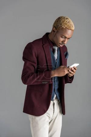 african american man using martphone on grey background