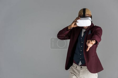 african american man with vr glasses with arm outstretched on grey background