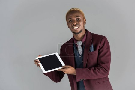 smiling african man holding digital tablet in hands  isolated on grey