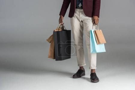 Photo pour Section basse de l'homme avec des sacs à provisions en papier sur fond gris - image libre de droit