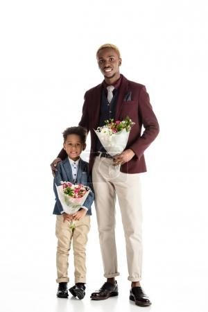 Yong african man and kid standing with flowers in hands isolated on white