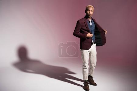 Photo for Young african man in red jacket standing on pink background - Royalty Free Image