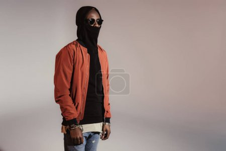 Stylish young african american man wearing hood with face mask