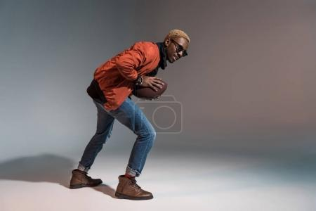Stylish young african american man holding rugby ball preparing to run