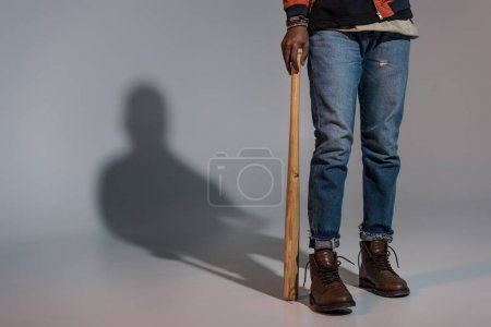 Partial view of guy leaning on baseball bat