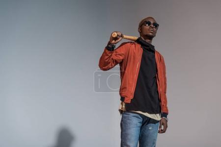 Photo pour Élégant jeune homme afro-américain tenant la batte de baseball - image libre de droit
