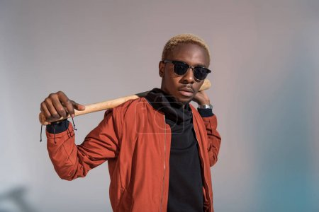 Stylish young african american man holding baseball bat on his shoulders