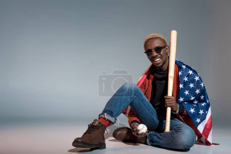 cheerful young african american man with us flag on shoulders holding baseball bat and ball on grey