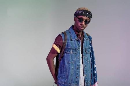 portrait of stylish young african american man in sunglasses looking at camera isolated on grey