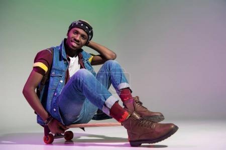 bel homme afro-américain jeune élégant assis sur une planche à roulettes et souriant à la caméra sur fond gris