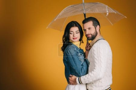attractive couple with transparent umbrella isolated on yellow