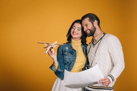 smiling couple looking at wooden plane isolated on yellow