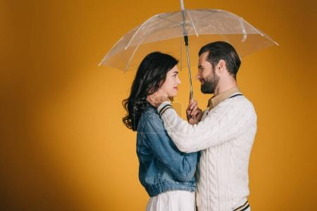couple hugging under transparent umbrella isolated on yellow