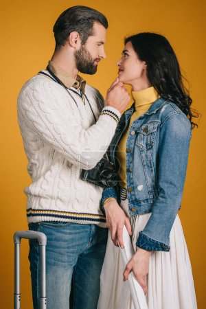 attractive couple looking at each other isolated on yellow