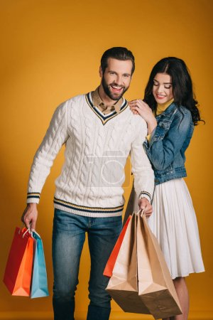Photo for Happy couple with shopping bags isolated on yellow - Royalty Free Image