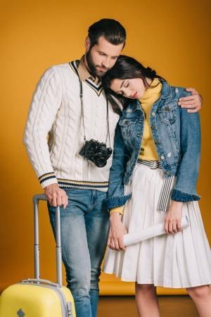 Photo pour Couple fatigué de touristes avec sac de voyage sur jaune - image libre de droit