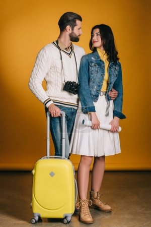 happy couple of tourists with travel bag on yellow