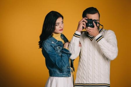 boyfriend taking photo with film camera isolated on yellow