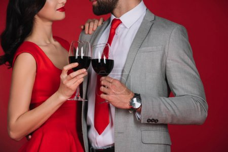 cropped image of couple clinking with glasses of wine and looking at each other isolated on red