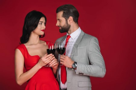 Photo for Couple clinking with glasses of wine and looking at each other isolated on red - Royalty Free Image