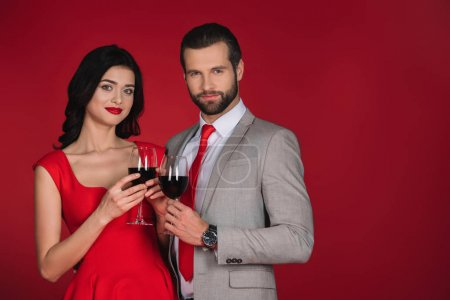 couple holding glasses of wine and looking at camera isolated on red