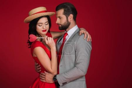 girlfriend holding heart shaped lollipop and hugging boyfriend isolated on red