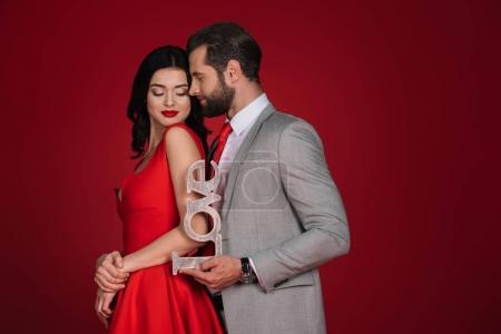 Foto de Atractiva pareja permanente con amor signo aislado en rojo - Imagen libre de derechos