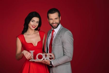 smiling couple standing with sign love isolated on red
