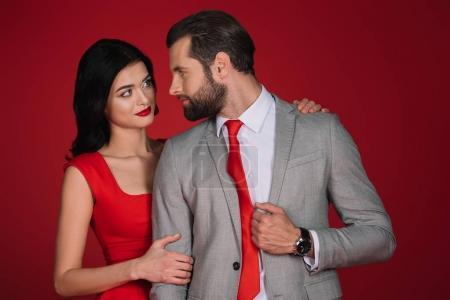 girlfriend hugging boyfriend isolated on red