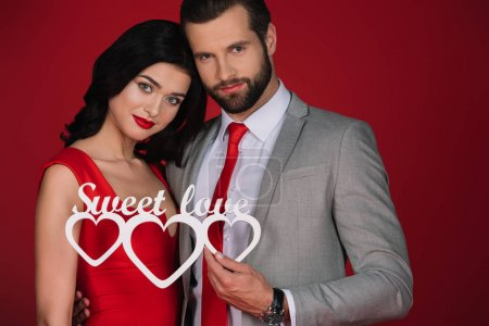 attractive couple holding sign sweet love isolated on red