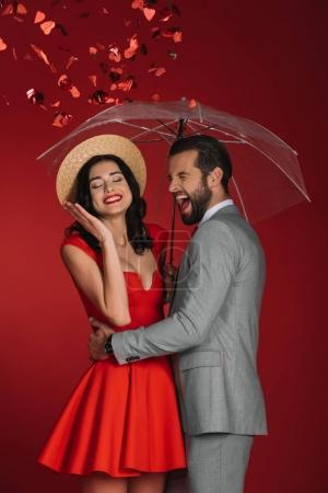 laughing couple hiding under umbrella from falling confetti isolated on red