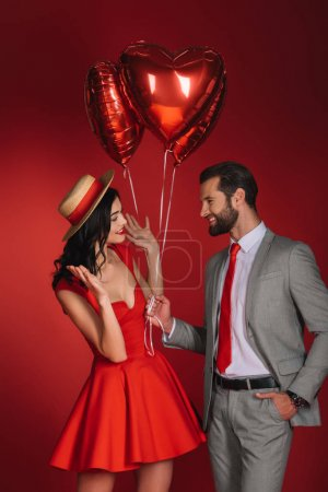 boyfriend presenting balloons to girlfriend isolated on red
