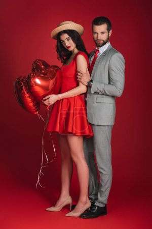 attractive couple with heart shaped balloons looking at camera on red