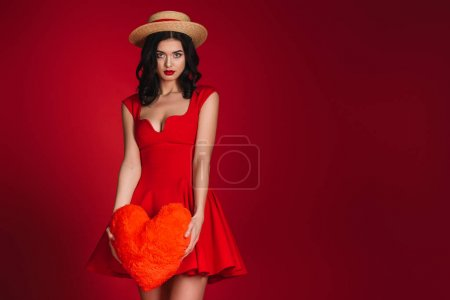 attractive girl in red dress holding heart shaped pillow isolated on red