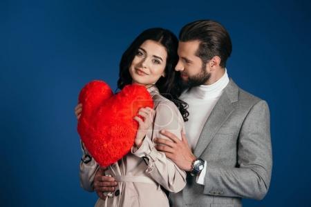 Photo pour Petite amie tenant oreiller en forme de coeur et petit ami embrassant son isolé sur bleu - image libre de droit