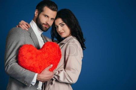 Foto de Atractiva pareja sosteniendo la almohada en forma de corazón aislado en azul - Imagen libre de derechos