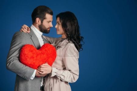 Foto de Pareja con corazón en forma de almohada y mirando mutuamente aisladas en azul - Imagen libre de derechos