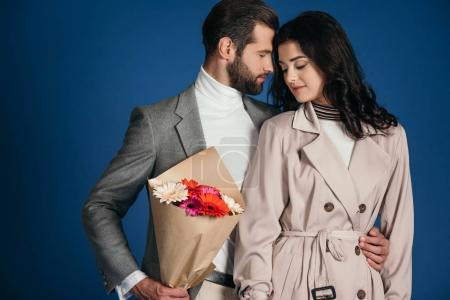 boyfriend hugging girlfriend and presenting bouquet isolated on blue