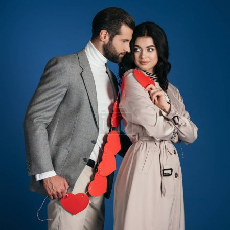 attractive couple holding garland of red hearts isolated on blue