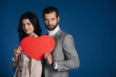 couple holding heart shaped piece of paper isolated on blue
