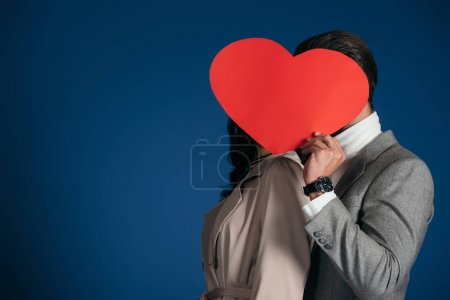 couple covering faces with heart shaped piece of paper isolated on blue